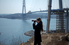 Young woman looking through binoculars on background of construction of cable-stayed bridge Stock Photos