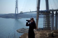 Young woman looking through binoculars on background of construction of cable-stayed bridge Stock Photo