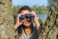 Woman looking through binoculars  near trees Stock Image