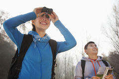 Young woman looking through binoculars, man standing in the background Stock Image