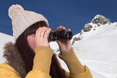 Young woman looking through binoculars in the mountains Stock Photo