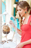 Young woman looking at birds in white cage Royalty Free Stock Photos
