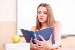 Young woman looking upon blue copy book Stock Photo