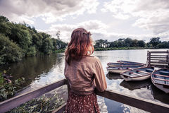 Young woman looking at boats in lake. A young woman is looking at some rowing boats in a lake royalty free stock image