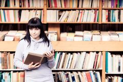 Young Woman Looking At Books In A Bookstore. A young woman is looking at books in a bookstore Stock Photo