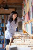 Young Woman Looking At Books In A Bookstore. A young woman is looking at books in a bookstore Royalty Free Stock Photography