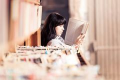 Young Woman Looking At Books In A Bookstore. A young woman is looking at books in a bookstore Royalty Free Stock Photos