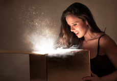 Young woman looking into a box Royalty Free Stock Images