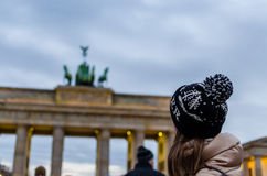 Young woman looking on Brandenburg Gate in Berlin. In winter. The Brandenburg Gate (German: Brandenburger Tor) is a former city gate, rebuilt in the late 18th stock images