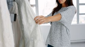 Woman looking at bridal gowns on display in boutique royalty free stock image