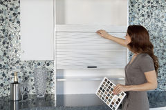 Young woman looking at cabinets in contemporary kitchen while holding color samples Royalty Free Stock Photo