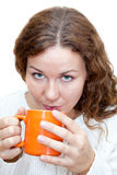 Young woman looking at camera and drinking from orange mug Royalty Free Stock Photography