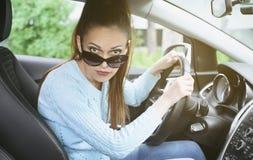 Young woman looking at camera while driving a car Stock Photo