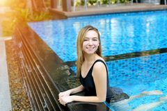 Young woman looking at camera enjoy swimming at blue pool outdoors, relaxing near palms and apartment building in stock photography