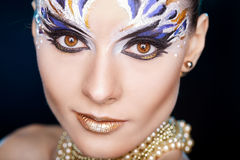 Young woman looking at the camera with fantasy make up face art studio shot. Copy space. High resolution stock photography