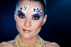Young woman looking at the camera with fantasy make up face art studio shot. Royalty Free Stock Photography