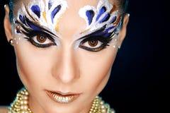 Young woman looking at the camera with fantasy make up face art studio shot. Royalty Free Stock Photos