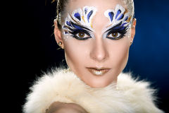 Young woman looking at the camera with fantasy make up face art studio shot. Royalty Free Stock Images