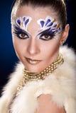 Young woman looking at the camera with fantasy make up face art studio shot. Royalty Free Stock Image