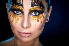 Young woman looking at the camera with fantasy make up face art studio shot. Royalty Free Stock Photo