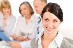 Young woman looking camera during meeting. Young executive women looking camera during meeting with team colleagues Stock Photography