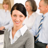 Young woman looking camera during meeting. Young executive women looking camera during meeting with team colleagues Stock Photos