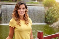 Young woman looking at camera near park waterfall Stock Photos