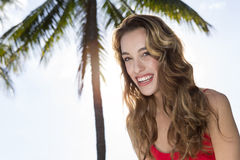 Young woman looking at the camera, palm tree Royalty Free Stock Image