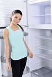 Young woman looking at camera shelf in fridge. Stock Image