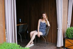 Young woman looking at camera and smiling near cafe with close royalty free stock photo
