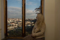 Young woman looking on the city from window Royalty Free Stock Photo