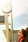 Young woman looking at clock at train station Royalty Free Stock Image