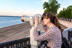 Young woman looking through the coin operated binocular. Samara, Russia - May 19, 2018: Young woman looking through the coin operated binocular on the bank of Royalty Free Stock Images