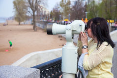 Young woman looking through the coin operated binocular Royalty Free Stock Photos