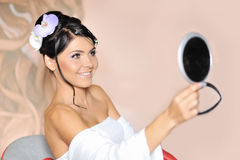 Young woman looking in cosmetic mirror Royalty Free Stock Images