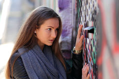 Young woman looking curiously through a door. Beautiful girl wearing leather jacket on the street stock photos