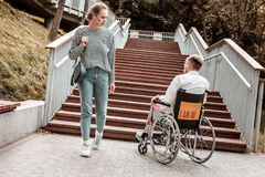 Young woman looking at the disabled man sitting in the wheelchair. Unusual problem. Serious young women passing the invalid men sitting in the wheelchair in royalty free stock photos