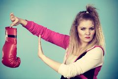 Disgusted woman holding boxing glove Stock Image