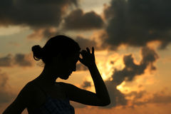 Young woman looking at the distance. With her hand over her face. Back lit with golden sunset background Stock Image