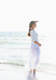 Young woman looking into distance on sea shore Royalty Free Stock Images