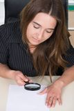 Young woman is looking at a document through a magnifier Royalty Free Stock Photo
