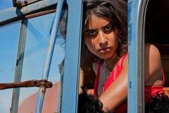 Young woman looking between door jam Stock Photos