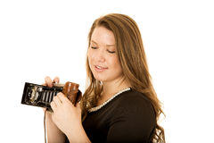 Young woman looking down at an antique camera Royalty Free Stock Photos