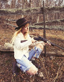 Young woman looking down the barrel of a gun. In the woods with a fence behind her Royalty Free Stock Photography
