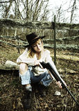 Young woman looking down the barrel of a gun. In the woods with a fence behind her Stock Photography