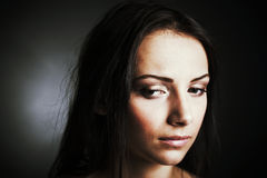 Young woman looking down. Closeup  of a reflective young woman  looking down Stock Image