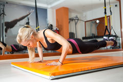 Young woman looking down while doing push-ups. Young woman doing push-ups while legs hanging on elastic rope stock image