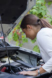 Young woman looking down the engine of a car Royalty Free Stock Photography