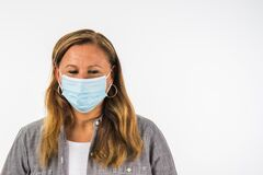 Young Woman Looking Down With Face Mask For Protection From Corona Virus