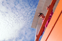 Young woman looking down from a lifeguard watchtower. With a beautiful blue sky full of a clouds Stock Photos